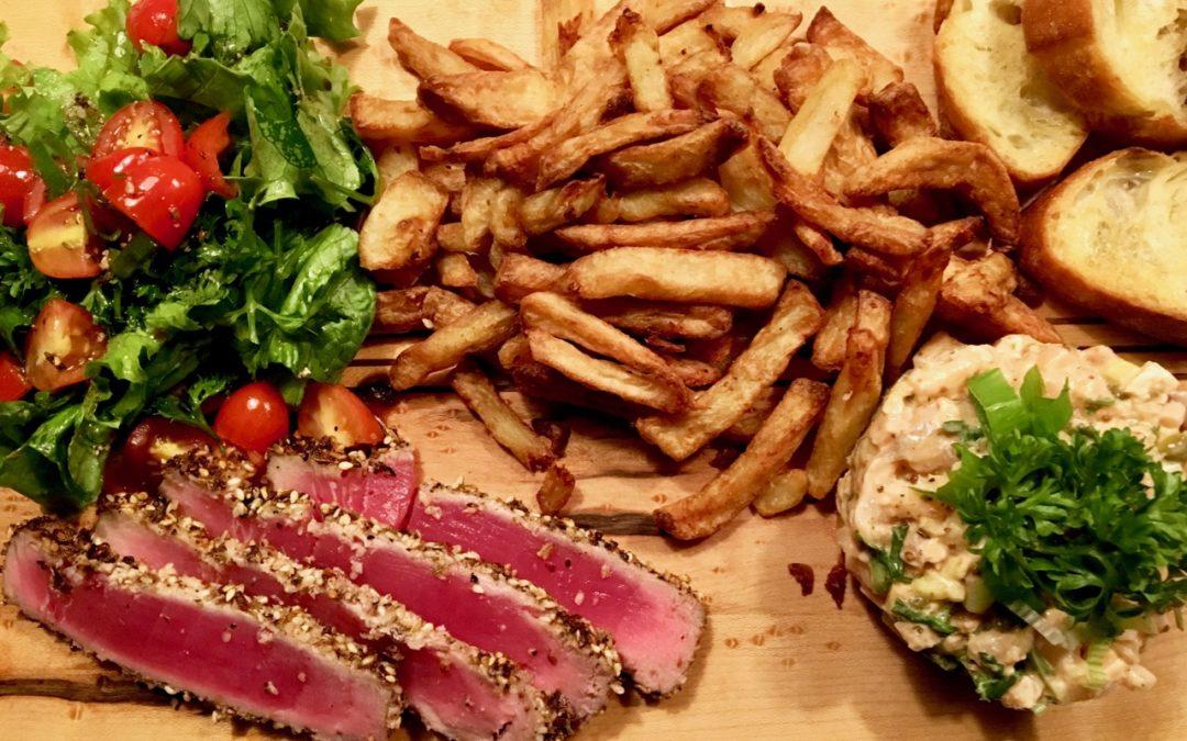 Tataki de thon frites salade avec tomates, tartare de saumon et croûtons de pain