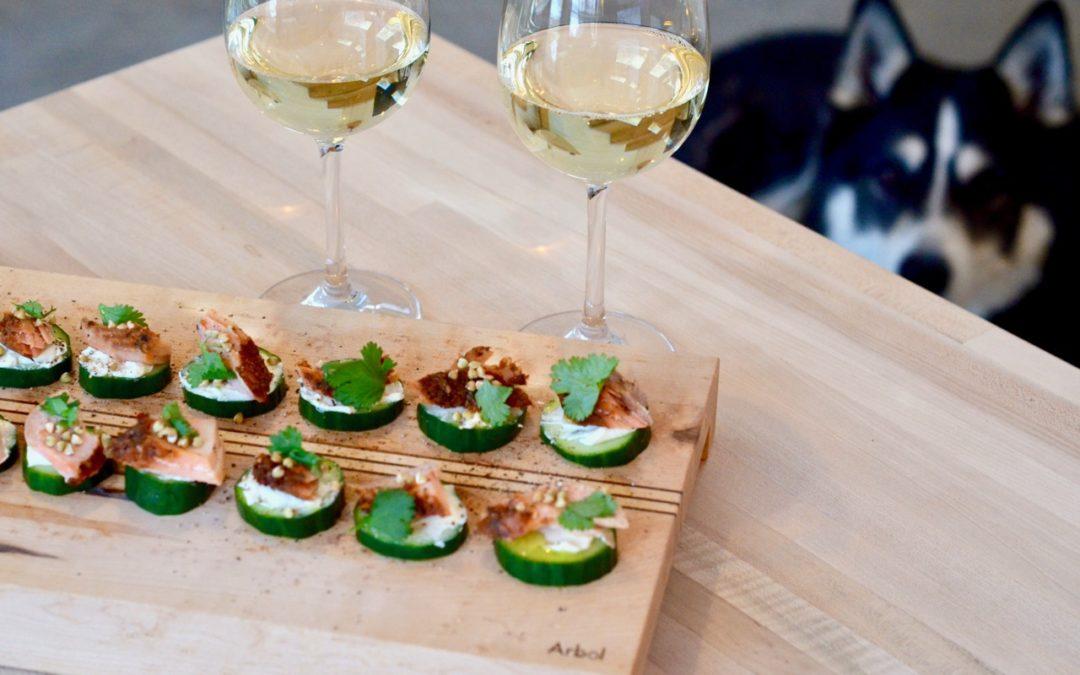Concombres avec saumon fumé fromage à la crème coriandre, sarrasin sur une planche de bois et du vin blanc
